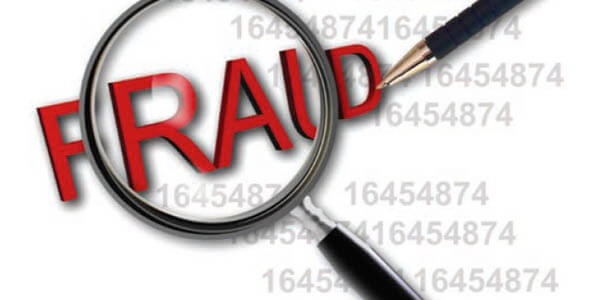 """The word """"FRAUD"""" under a magnifying glass"""