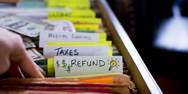 "Photo of a drawer of files that read ""Taxes"" and ""Refund"""