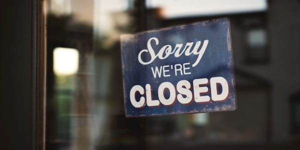 """Photo of a sign hanging in a store window that reads """"Sorry, We're Closed"""""""